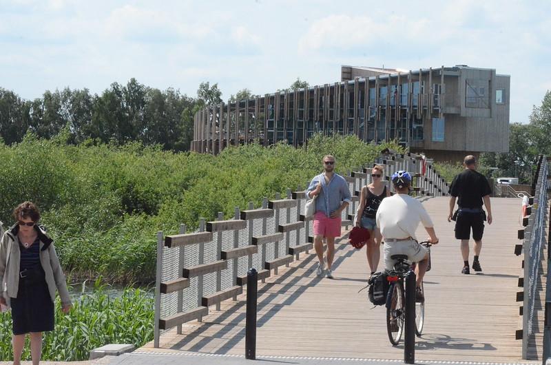 Ett trähus med en träbro där det rör sig flera människor.