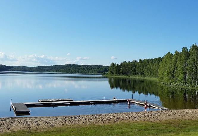 En badplats med stilla vatten, skog och en blå himmel.
