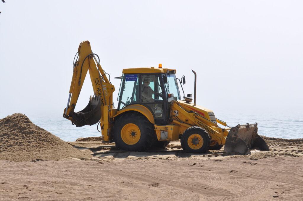 En orange grävskopa på en sandstrand med vatten i bakgrunden.