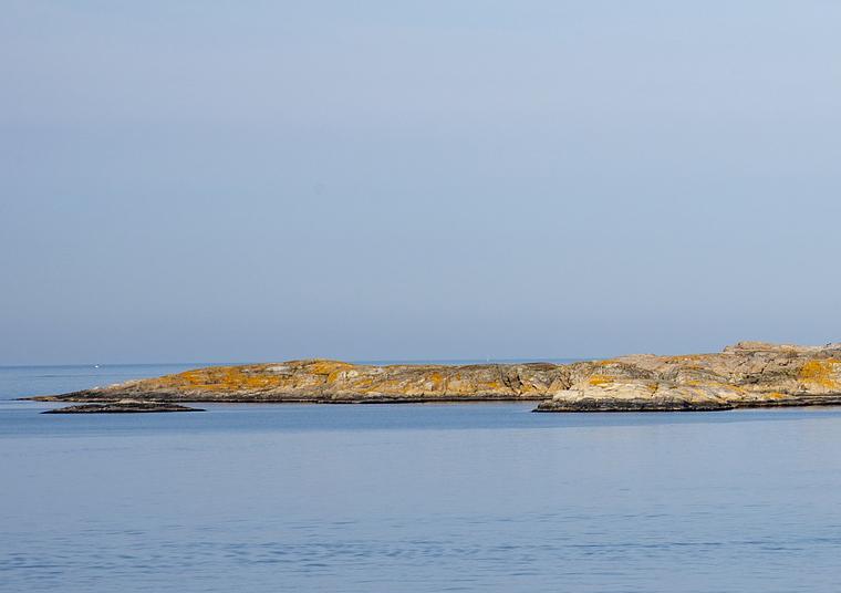Klippor vid havet med klarblå himmel.