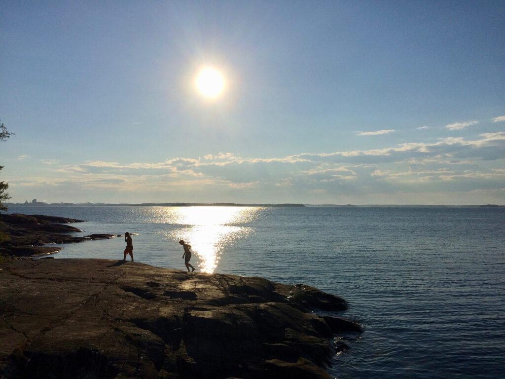 två barn som leker på klippor vid kusten.