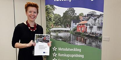 En kvinna med kort rött hår som håller i en rapport står vid en roll-up för LIFE IP Rich Waters.
