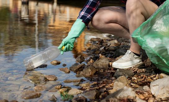 En människa som sitter på huk vid vatten med en plasthandske på handen som håller i en petflaska.