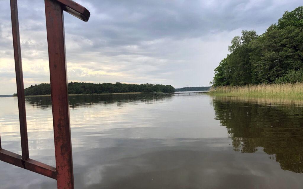 En stilla sjö med vass och öar, med ett rött staket i förgrunden.